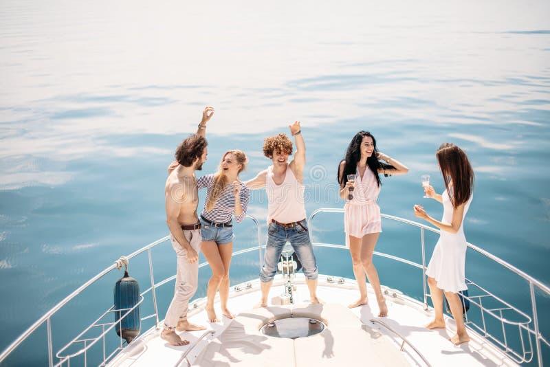 海洋巡航和假期-戴香槟眼镜的年轻人在小船或游艇 库存图片