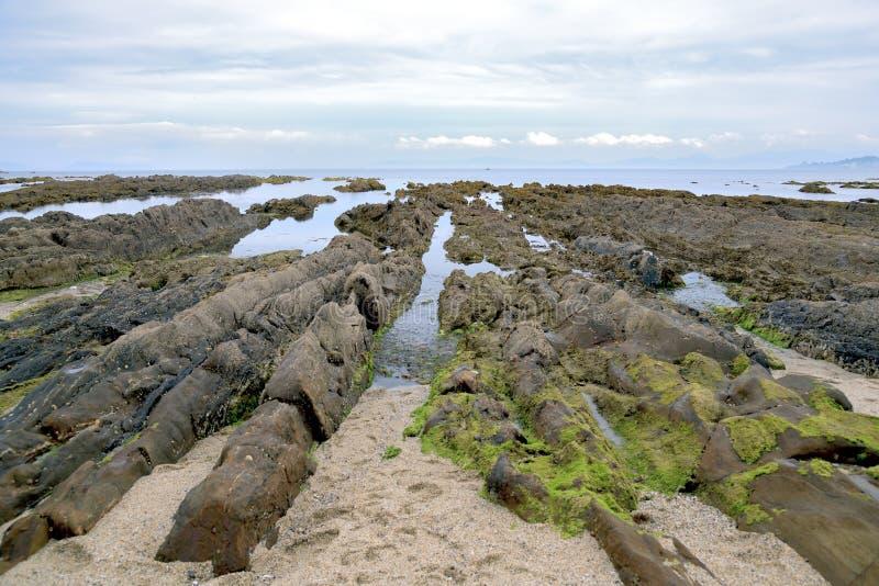 海洋日出风景有波状云和岩石的 自然,沙子 免版税库存图片