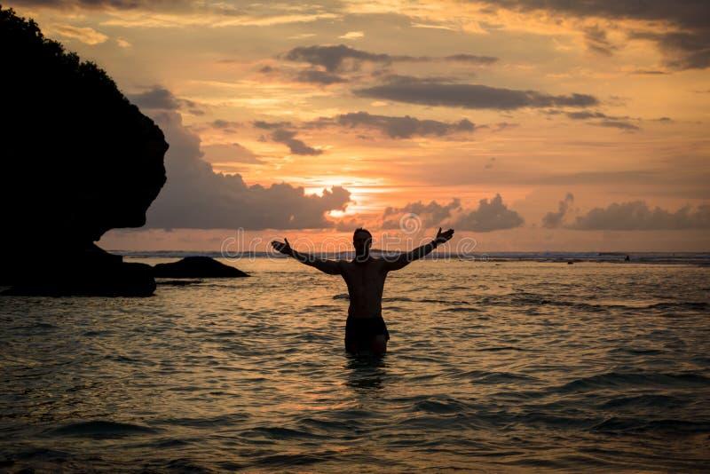 海洋的人享受在巴厘岛的日落有大开的胳膊的 免版税库存照片