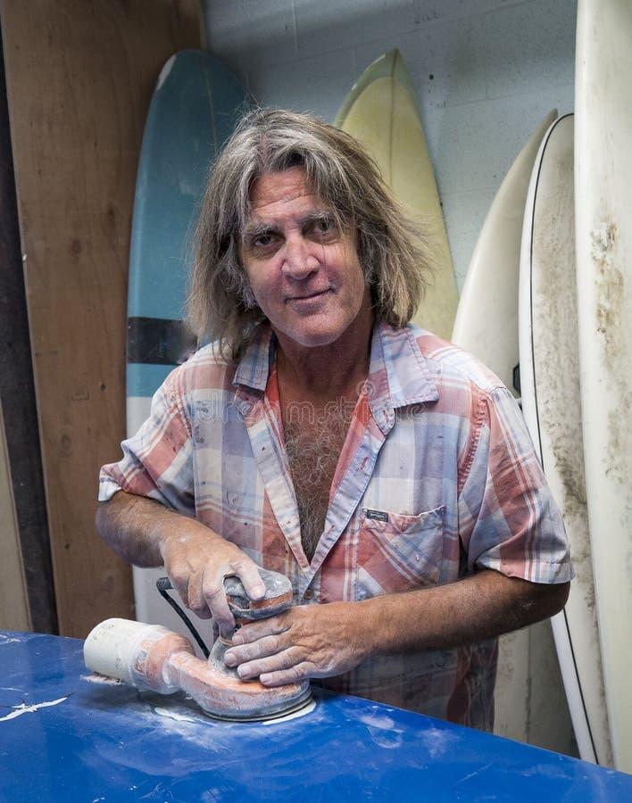 海浪修理专业工作在冲浪板 库存图片