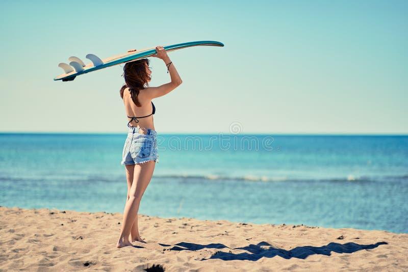 海浪女孩去冲浪寻找w的美丽的女孩冲浪者 免版税库存照片