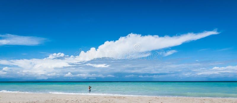 海浪的人 在海滩的温暖的下午在古巴 一个人在柔和的海洋海浪走在巴拉德罗角 免版税库存图片