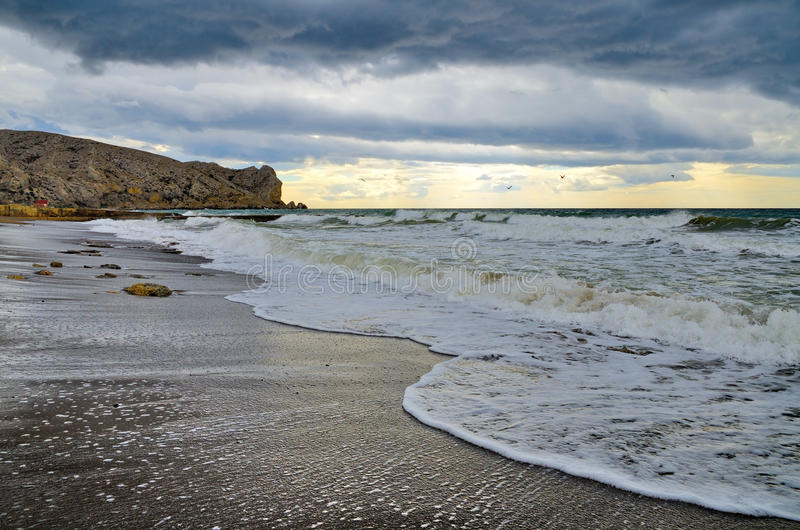 海浪的波浪在一个沙滩的在多云天气 克里米亚sudak 免版税图库摄影