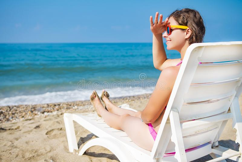 海海滩的少妇坐deckchair并且调查距离 夏天热带手段的女孩在海滩放松 免版税库存图片
