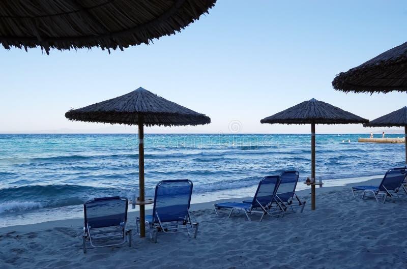 海海滩的看法与伞和sunbeds的在晚上 免版税图库摄影