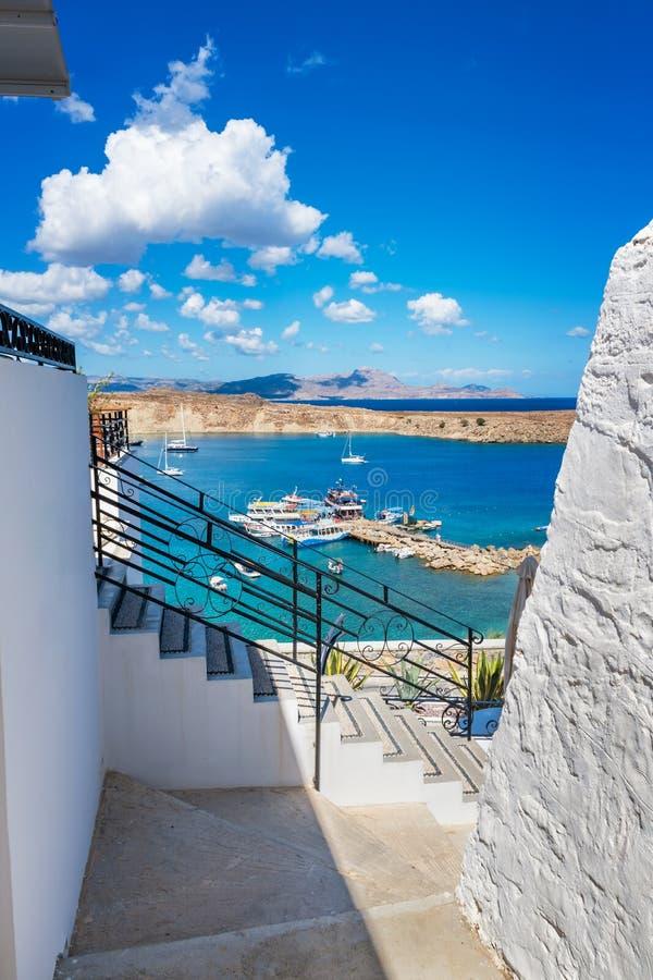 海湾看法从Lindos村庄罗得岛,希腊街道的  免版税库存照片