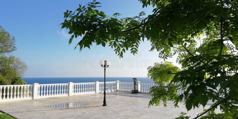 ?? 海滨城镇的堤防在一个晴朗的夏日通过树的绿色叶子反对天空蔚蓝的 免版税库存照片