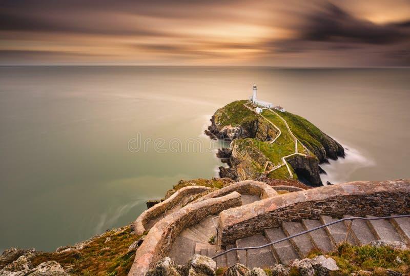 海滨岛屿上的灯塔,具有地平线和美丽的日落 库存图片