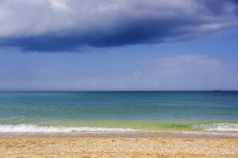 海滨的看法晴天和一朵阴沉的云彩 免版税库存图片