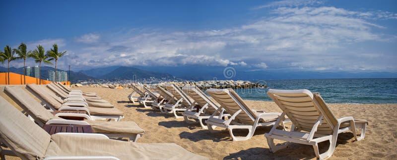 海滩、城市和海景在有海滩睡椅和海岸线的巴亚尔塔港墨西哥 图库摄影