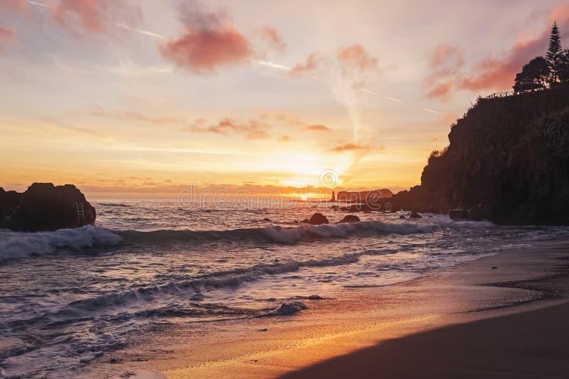 海滩上美丽的夕阳,黑色的火山沙 图库摄影