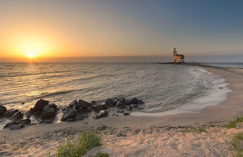 海滩上色灯塔日落 库存图片