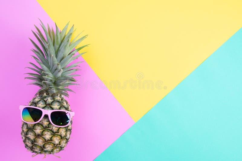 海滩与桃红色太阳镜的辅助部件菠萝在夏天休假和假期概念的桃红色,绿色和黄色背景 库存照片