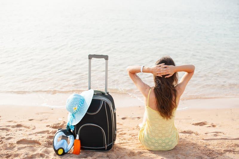 海滩享用夏天太阳的假日妇女坐在注视着愉快拷贝空间的沙子 E 免版税库存照片