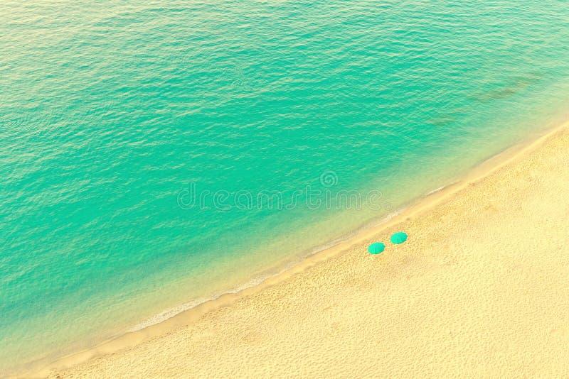 海滩休息室鸟瞰图有伞的在热带金黄天堂海滩用绿松石水 免版税库存照片