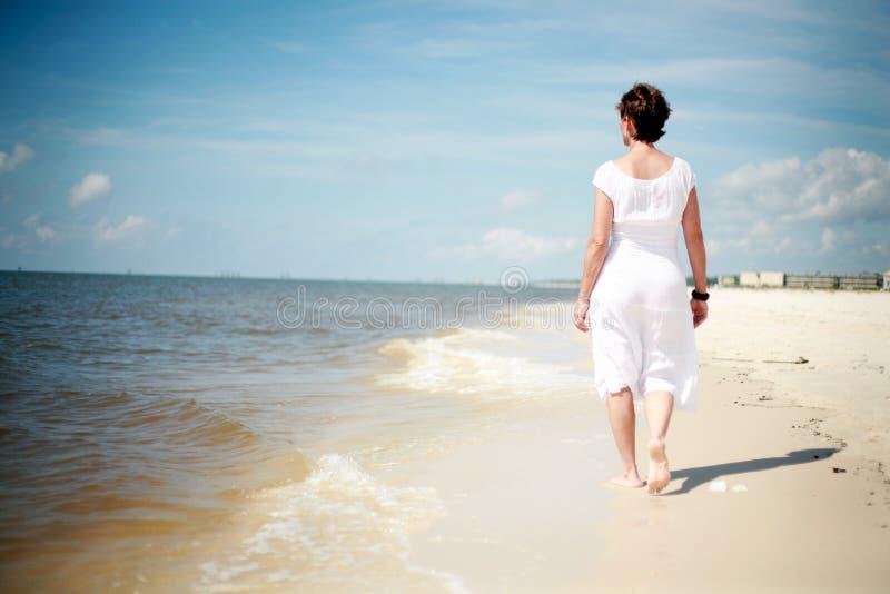 海滩俏丽的走的妇女 免版税库存照片
