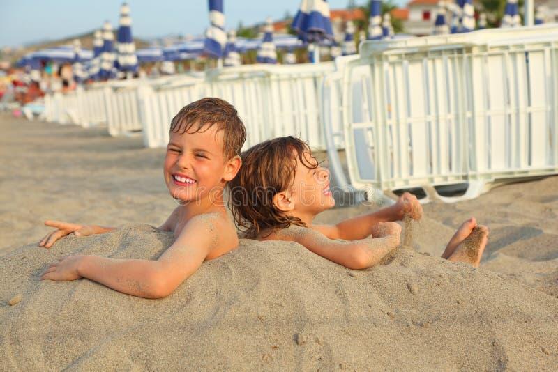 海滩兄弟被埋葬的沙子姐妹 库存照片