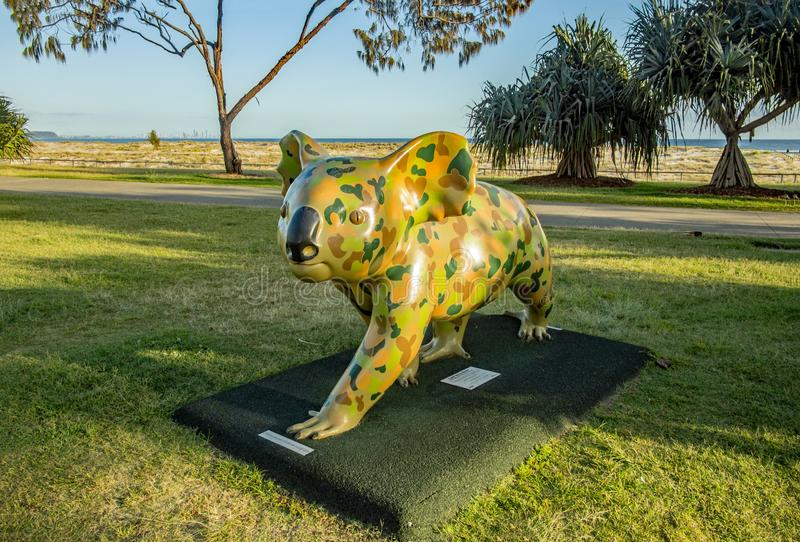 海滩入口戈尔德比尤特与为伪装颜色绘的考拉雕象的高层建筑物剪影昆士兰澳大利亚 图库摄影