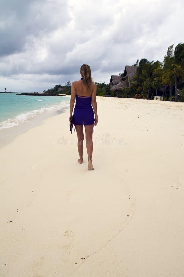海滩含沙走的妇女 免版税库存图片