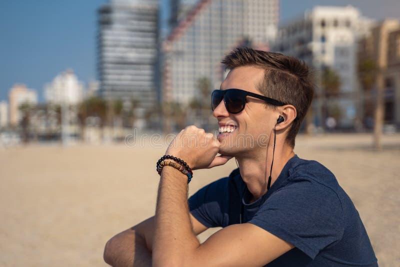 海滩听的音乐的年轻人与耳机 作为背景的城市地平线 库存图片