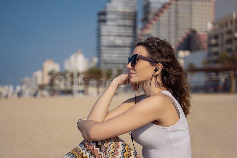 海滩听的音乐的年轻女人与耳机 作为背景的城市地平线 免版税库存图片