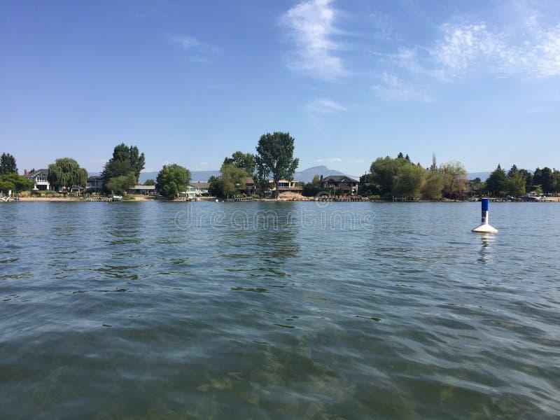 海滩和房子沿湖在湖风景背景中支持与浮体 库存图片