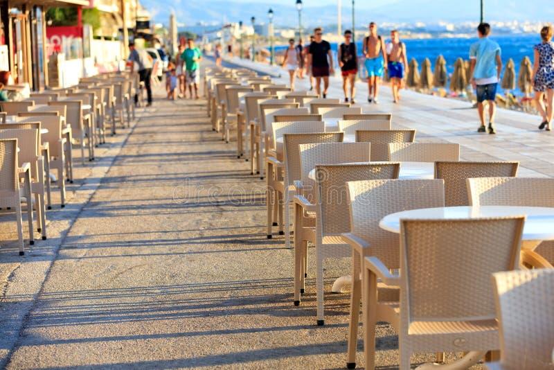 海滩咖啡厅的桌椅位于海滨长廊上,人们在蓝海边漫步,模糊 免版税库存照片