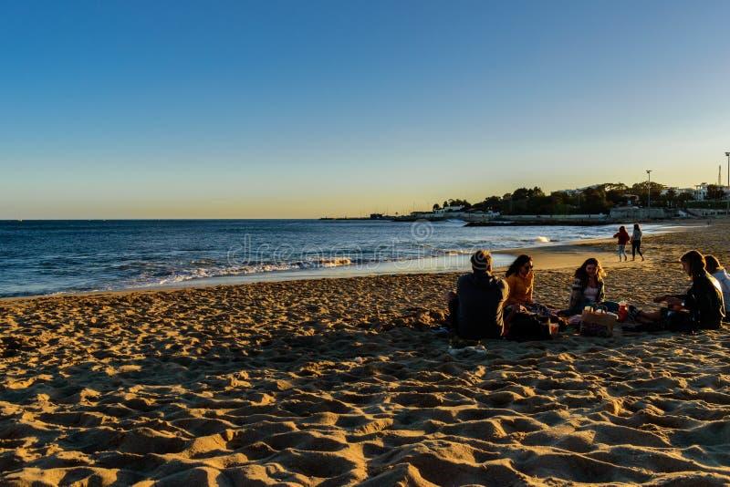海滩圣阿马鲁de奥埃拉斯- 2019年3月10日-在一起生活的小组朋友在下午末期坐Th沙子  免版税库存图片