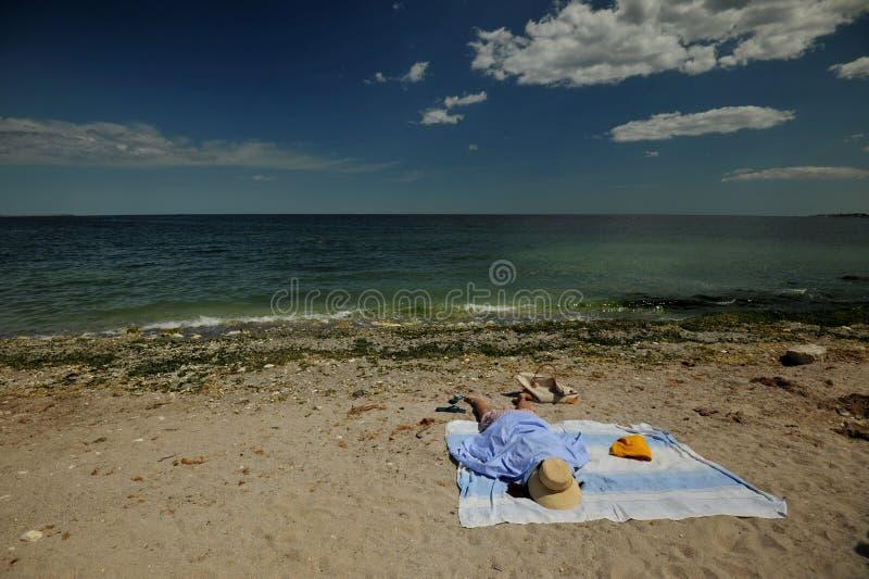 海滩在罗马尼亚,黑海在有妇女的康斯坦察市岸的 免版税图库摄影