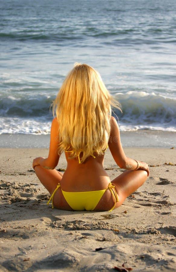 海滩坐的妇女 免版税库存照片