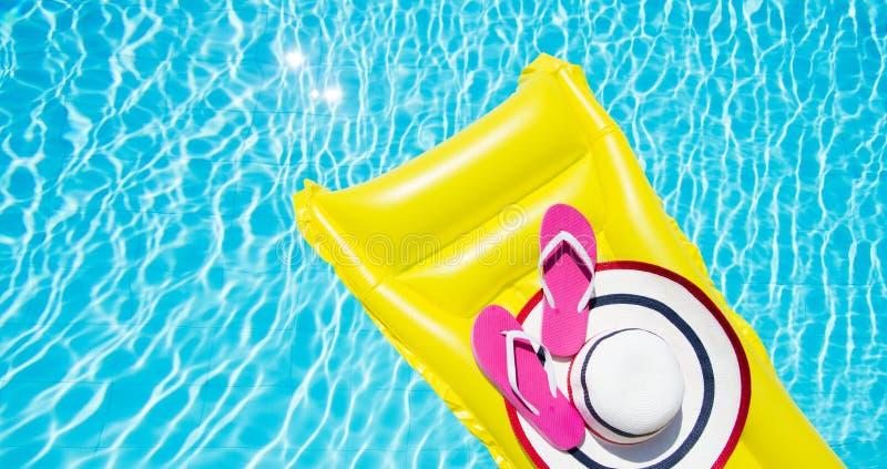 海滩夏天休假背景 可膨胀的气垫、触发器和帽子在游泳场 黄色lilo和夏令时 免版税库存照片