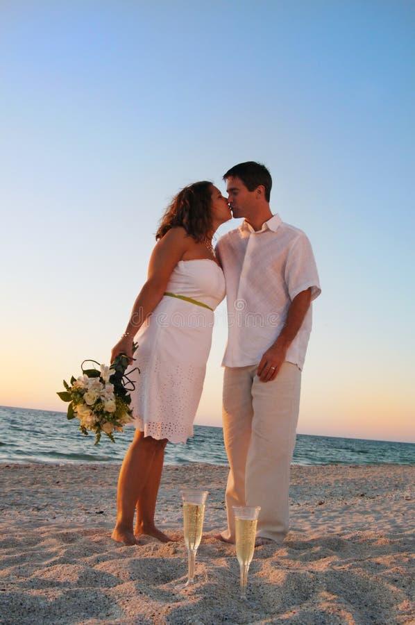 海滩夫妇亲吻婚礼 免版税库存图片