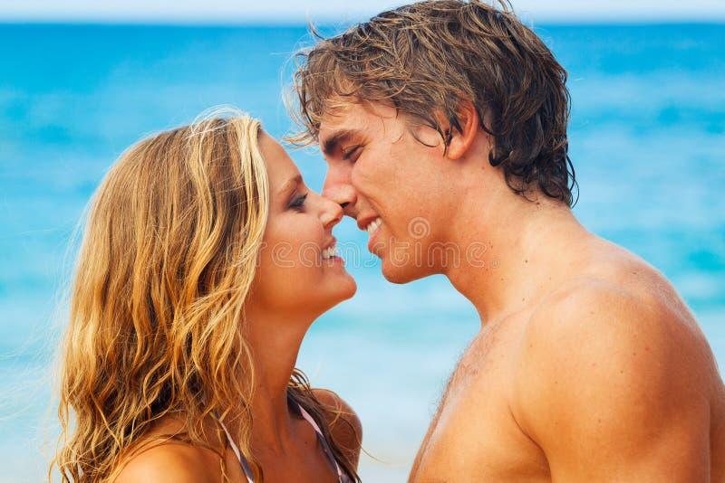 海滩夫妇亲吻的热带年轻人 库存照片
