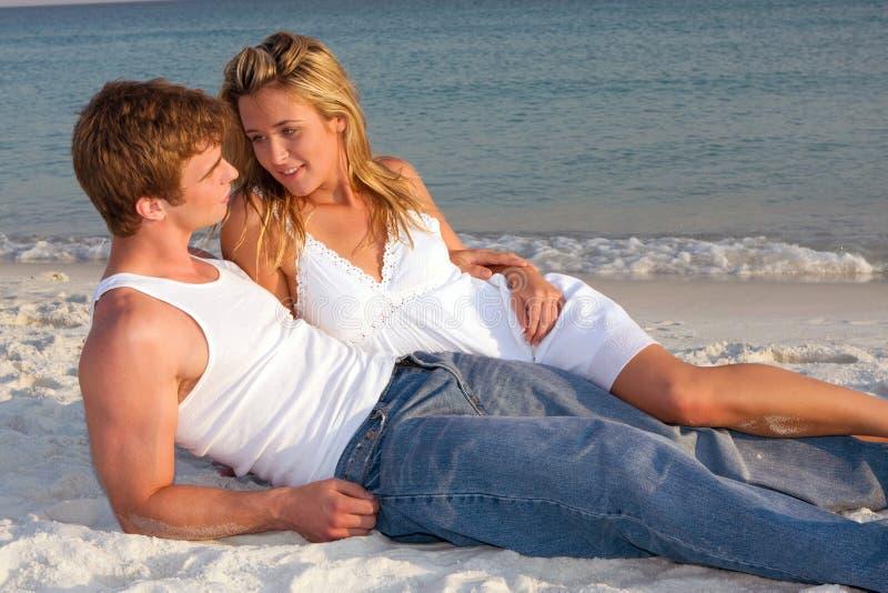 海滩夫妇位置日落 免版税库存照片