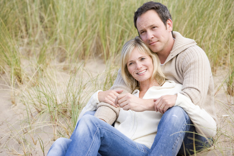 海滩夫妇坐的微笑 免版税库存照片