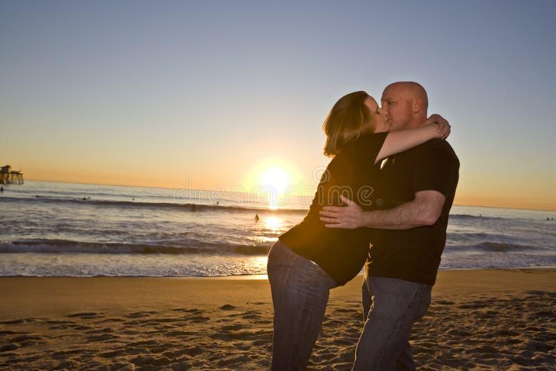 海滩夫妇怀孕的日落 免版税图库摄影