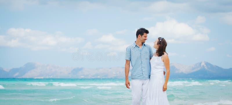 海滩夫妇愉快的走的年轻人 免版税库存照片