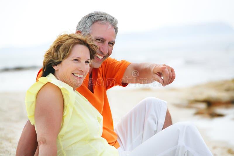海滩夫妇成熟坐 图库摄影