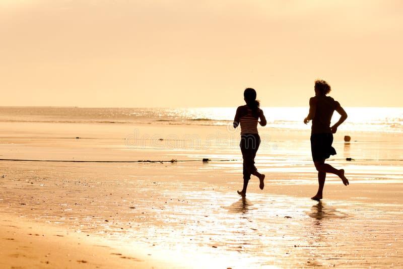 海滩夫妇跑步的体育运动 免版税库存照片