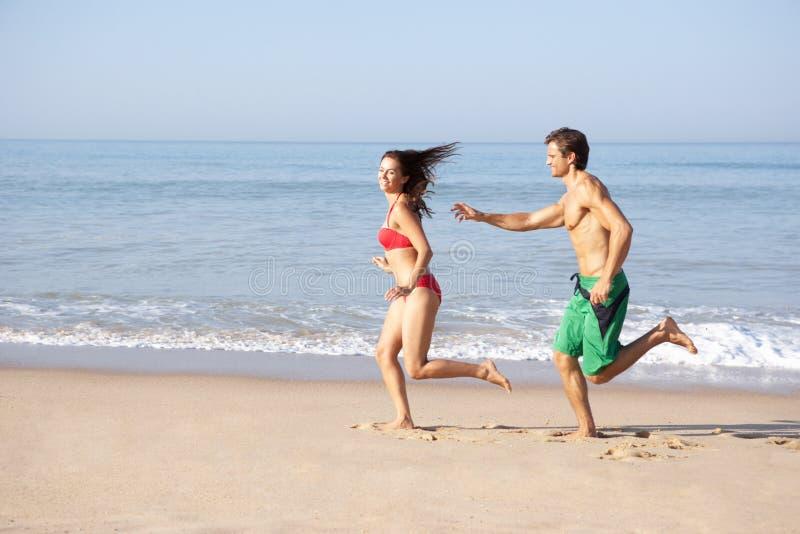 海滩夫妇运行的年轻人 免版税库存图片