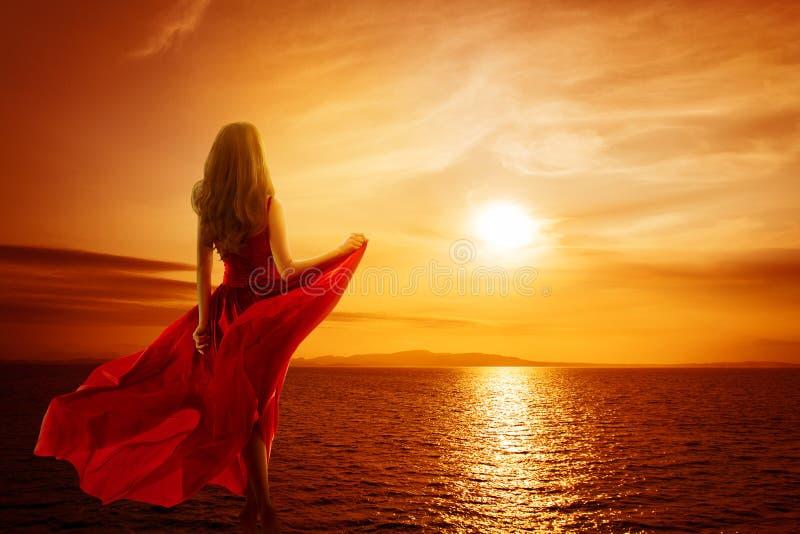 海滩女人看日落天空,穿红色招摇裙的女孩,背景 免版税库存照片