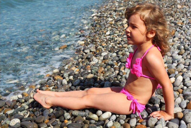 海滩女孩一点坐 免版税库存照片