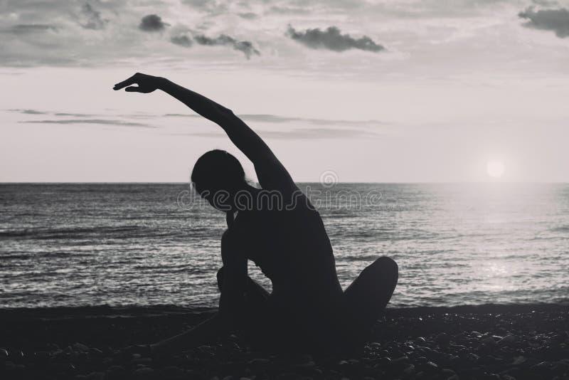海滩女孩实践的瑜伽 从后面的看法,剪影 黑色白色 库存图片