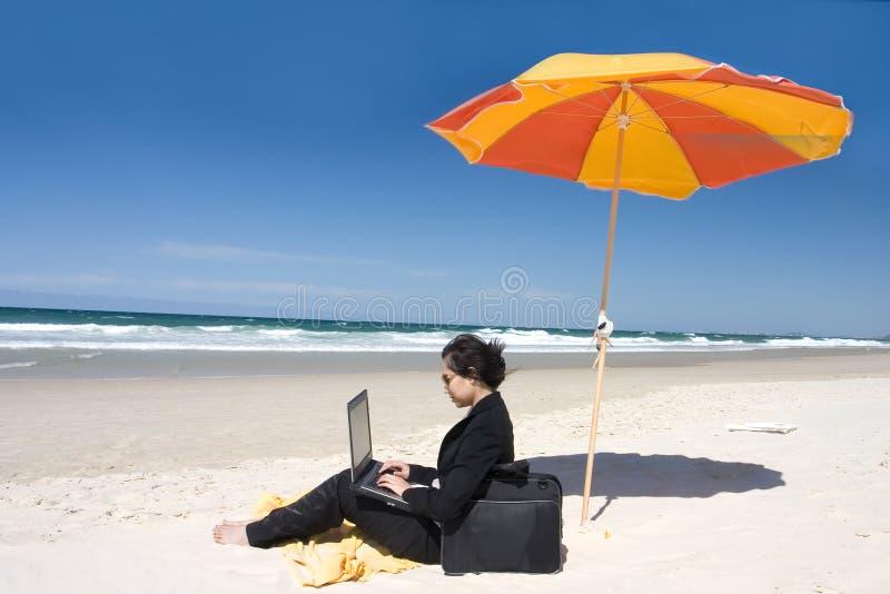 海滩女实业家工作 免版税库存照片