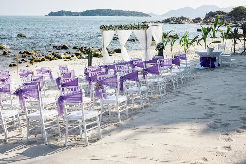海滩婚礼与白色chiavari椅子的地点设置用紫罗兰色透明硬沙框格装饰在海边 图库摄影