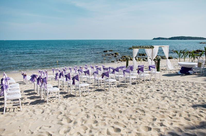 海滩婚礼地点设定了与白色chiavari椅子的海边与紫色透明硬沙框格装饰 库存照片