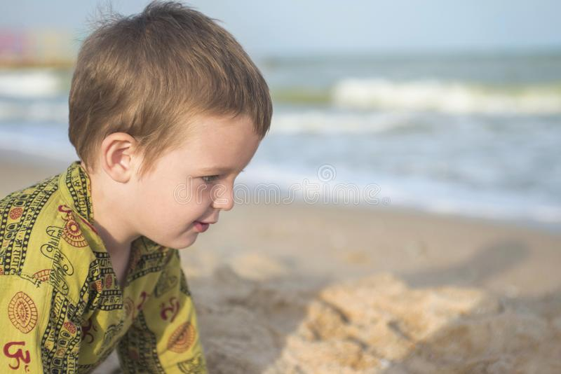 海滩孩子使用 与沙子的逗人喜爱的小男孩戏剧在海滩 库存图片