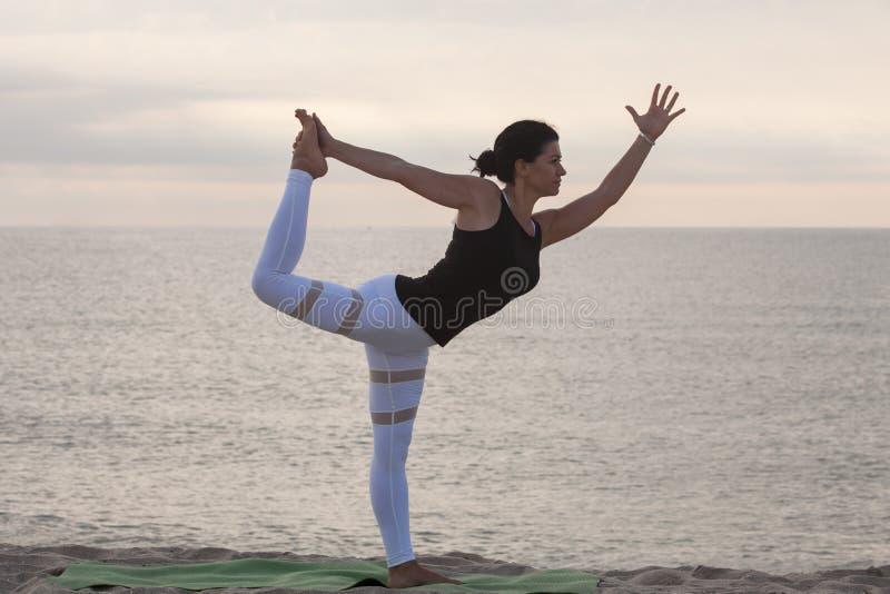 海滩实践的女子瑜伽 Dancer Pose, Natarajasana国王 户外体育 健康生活 库存照片