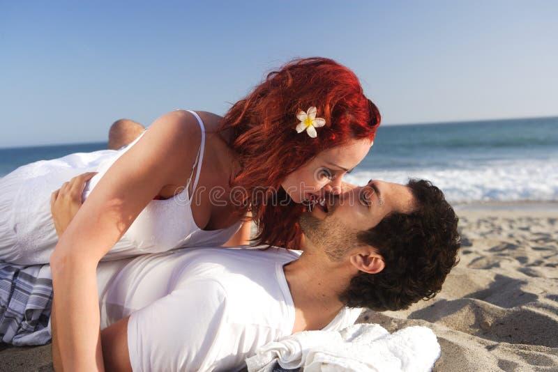 海滩对年轻人的夫妇亲吻 库存照片
