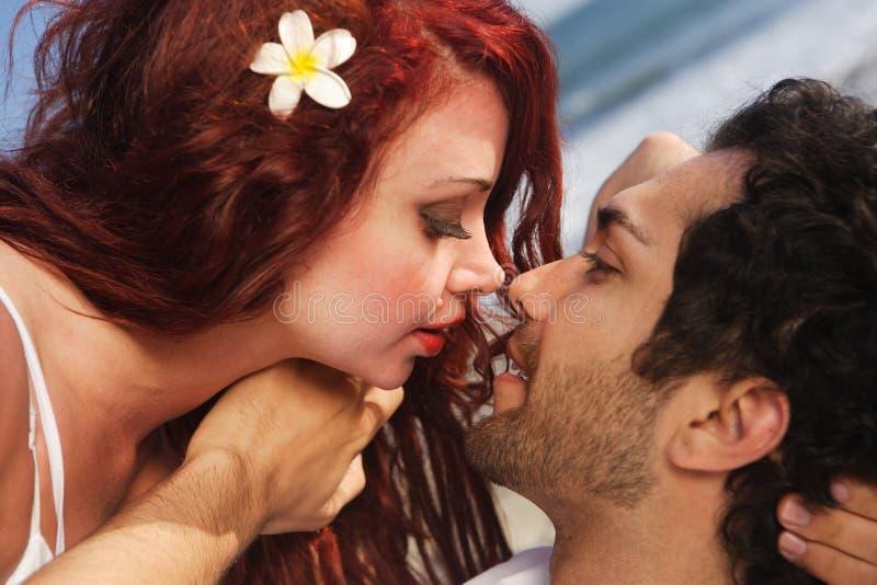 海滩对年轻人的夫妇亲吻 免版税图库摄影